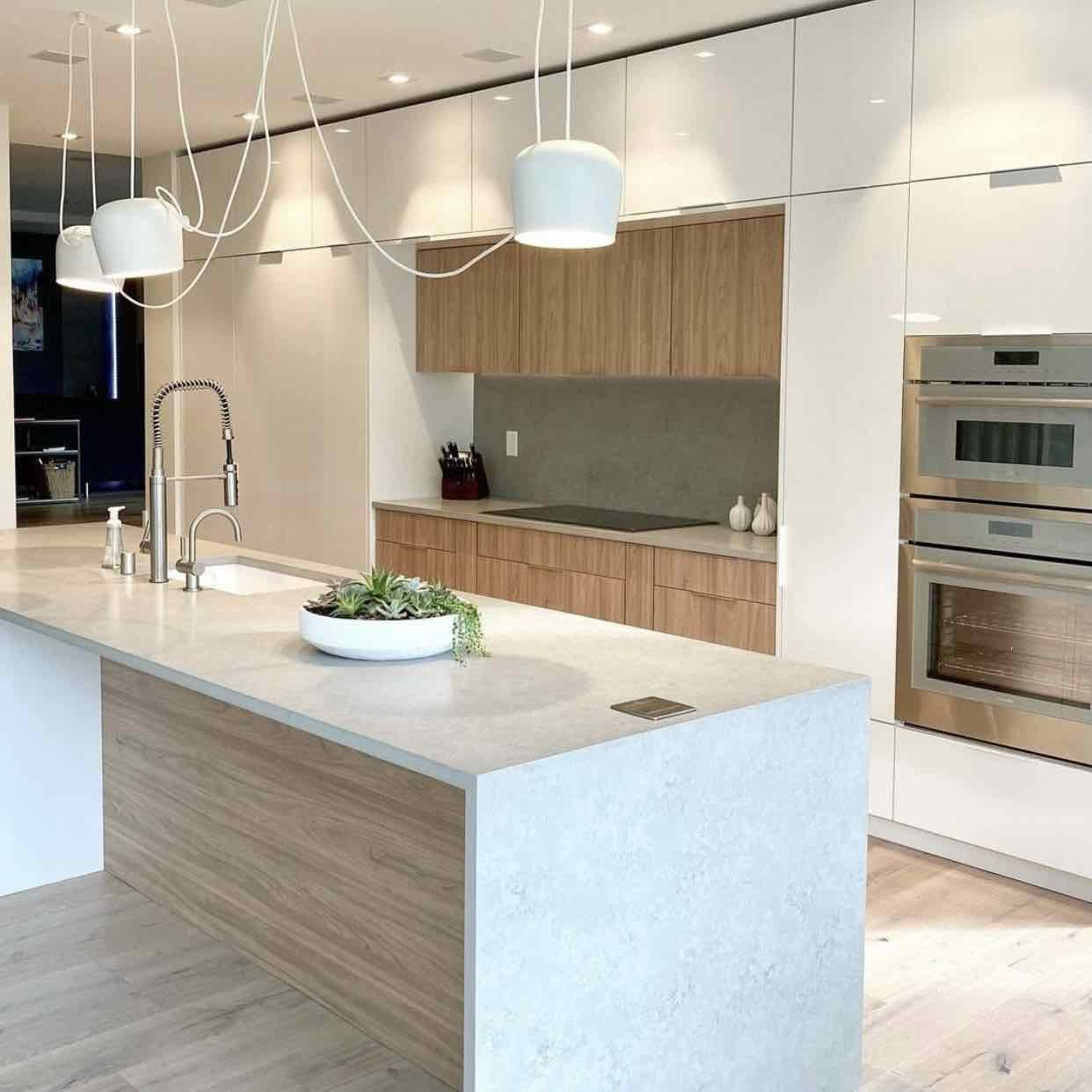 modern kitchen with white cabinets and light hardwood flooring